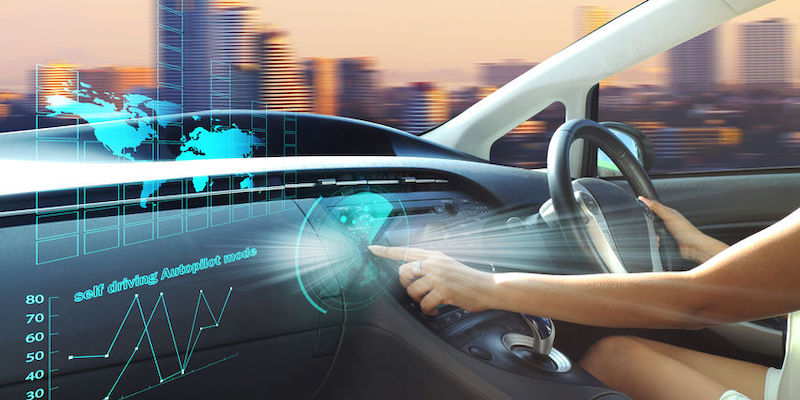 Self-driving autopilot mode, autonomous car, vehicle running in self-driving mode with a woman driver.