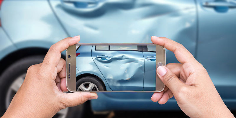 Closeup of a woman's hand holding a smartphone while taking a photo of a car accident.